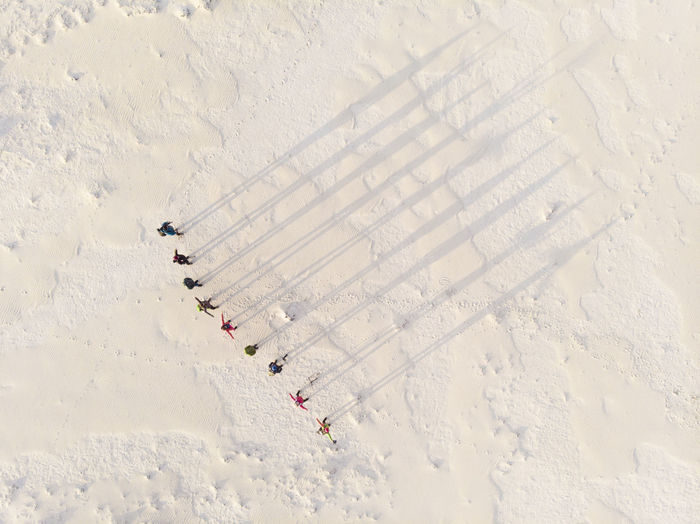 Aerial view of people standing on snow covered land