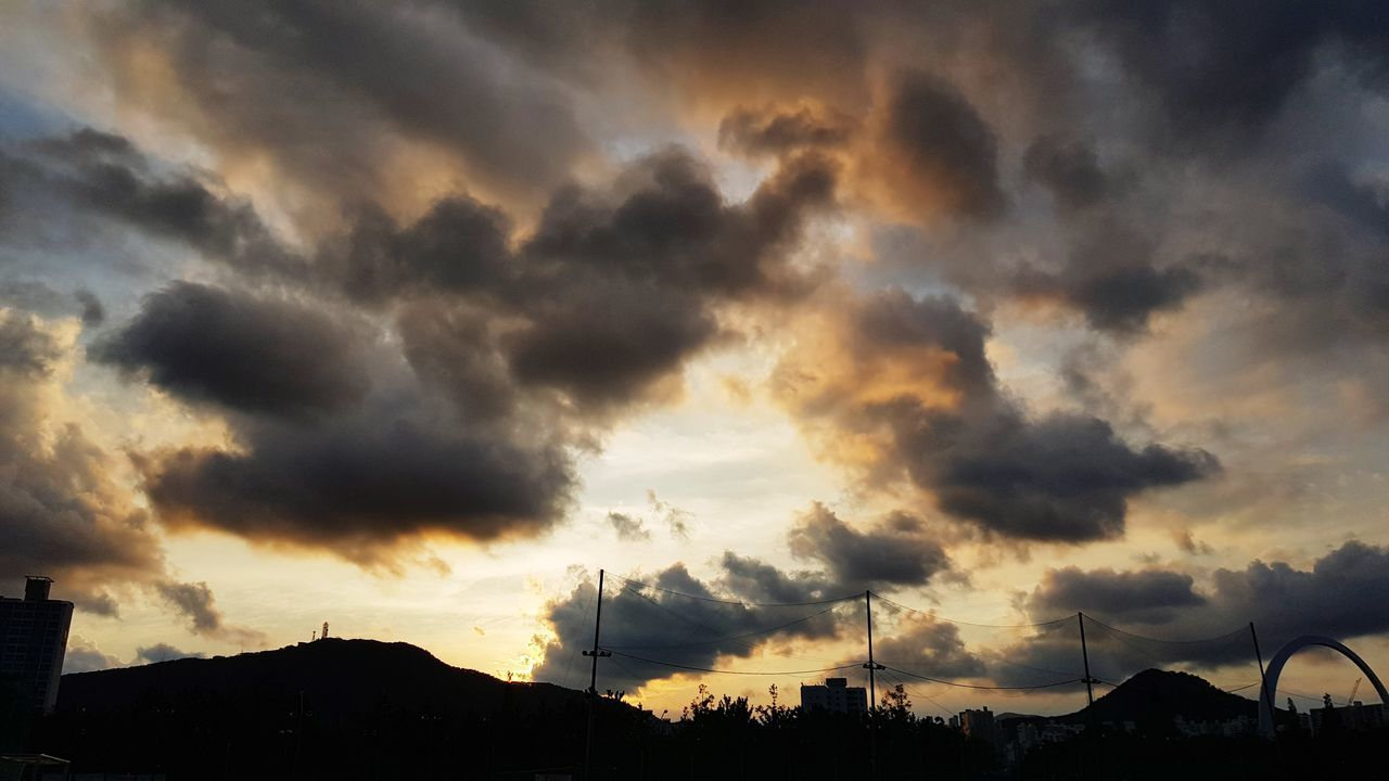 cloud - sky, sky, sunset, beauty in nature, scenics - nature, silhouette, nature, no people, dramatic sky, architecture, environment, tranquility, built structure, outdoors, orange color, overcast, building exterior, tranquil scene, low angle view, power in nature, ominous