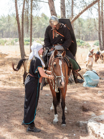 Tiberias, Israel, July 01, 2017 : Participants in the reconstruction of Horns of Hattin battle in 1187 one sits on a battle horse, and the second one holds a horse in the camp before the campaign near TIberias, Israel 1187 Army Battle Crusaders Defeat Equipment Field Guy De Lusignan Hattin Heat Heritage History Horn Horseman Israel Jerusalem KINGDOM Muslims Palestine Religion Saladin Templars Victory War Weapons