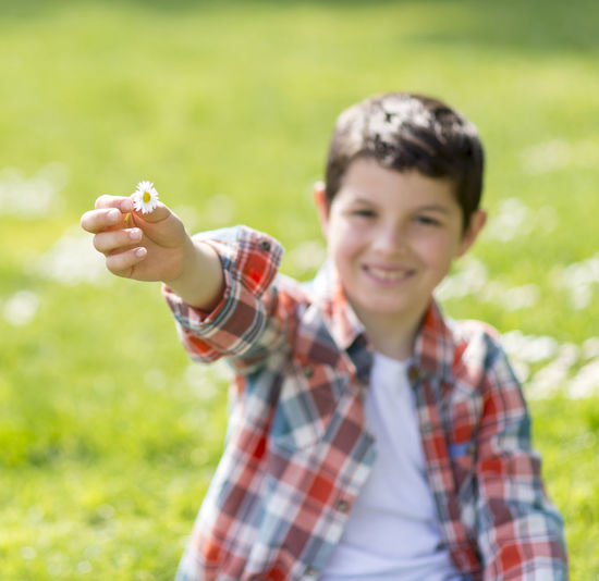 portrait of a casual teen boy, outdoors Portrait One Person Smiling Looking At Camera Holding Plant Leisure Activity Happiness Nature Child Waist Up Casual Clothing Front View Emotion Land Field Men Day Food And Drink Outdoors Pre-adolescent Child Plaid Shirt  Human Arm