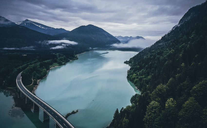 Aerial View Of Bridge Over River Amidst Mountains Against Cloudy Sky