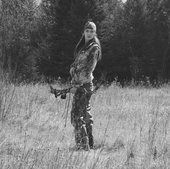 Side View Of Female Hunter With Archery Bow Standing On Field At Forest