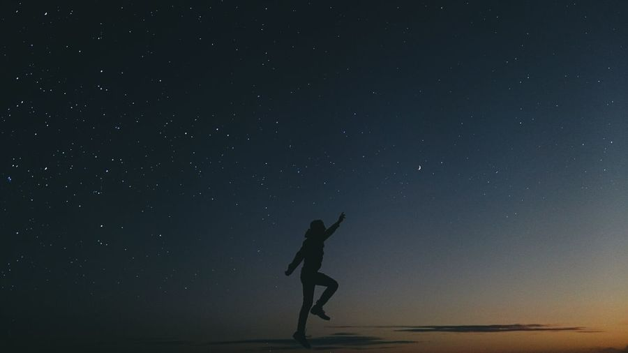 Silhouette of woman standing at night