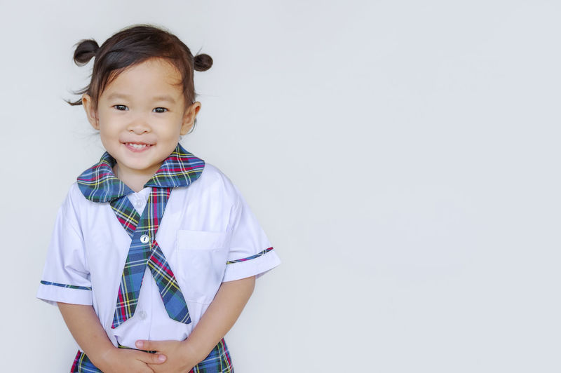 Happy cute asian little standing against white wall, with copy space. Activity ASIA Asian  Baby Beautiful Boy Cheerful Child Childcare Childhood Children Chinese Class Colorful Cute Education Fun Game Girl Happy Home Japanese  Kid Kindergarten Leisure Little Nursery People person Play Portrait Preschool Puzzle  Reading Room School Smile Table Toddler  Toy White Young