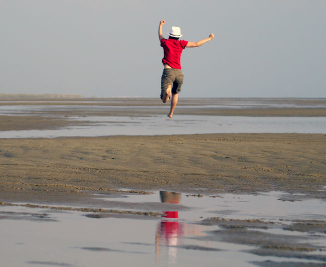 Rear view of man running on field against sky