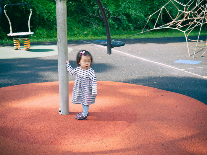 baby girl playing outdoor Casual Clothing Childhood Day Elementary Age Enjoyment Full Length Girls Leisure Activity Lifestyles Merry-go-round One Person Outdoors Park - Man Made Space People Playground Playground Equipment Playing Real People Standing Striped Tree