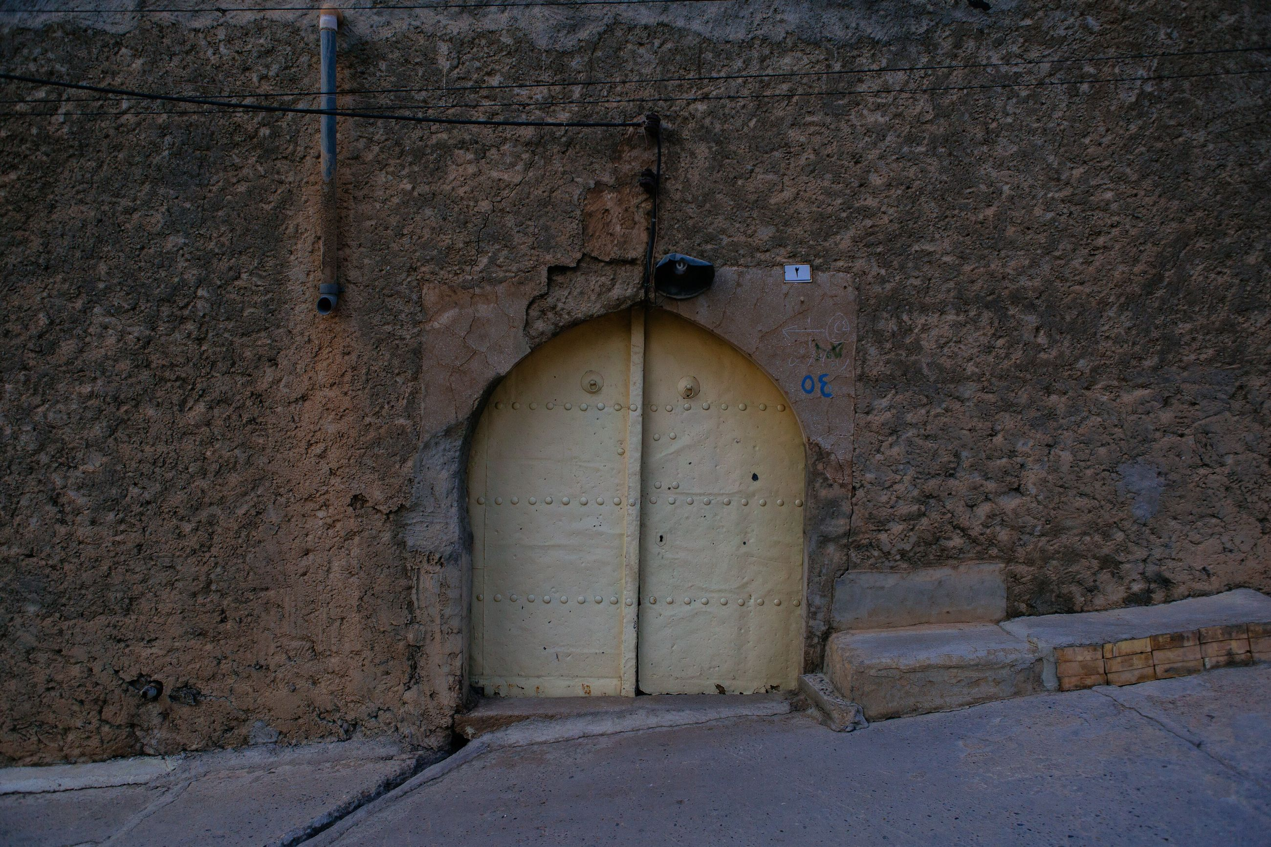 architecture, built structure, building exterior, wall - building feature, old, wall, stone wall, no people, lighting equipment, outdoors, day, street light, street, building, entrance, door, arch, brick wall, sunlight, religion