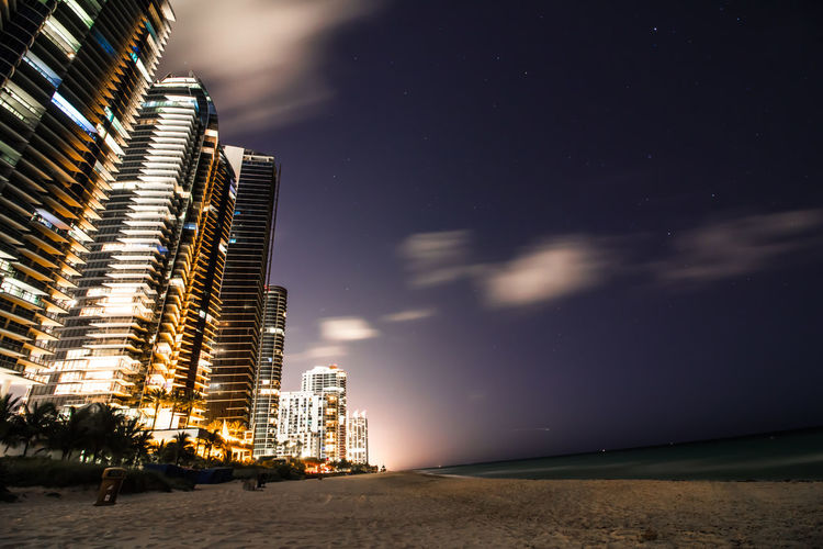 Buildings by beach in city at night