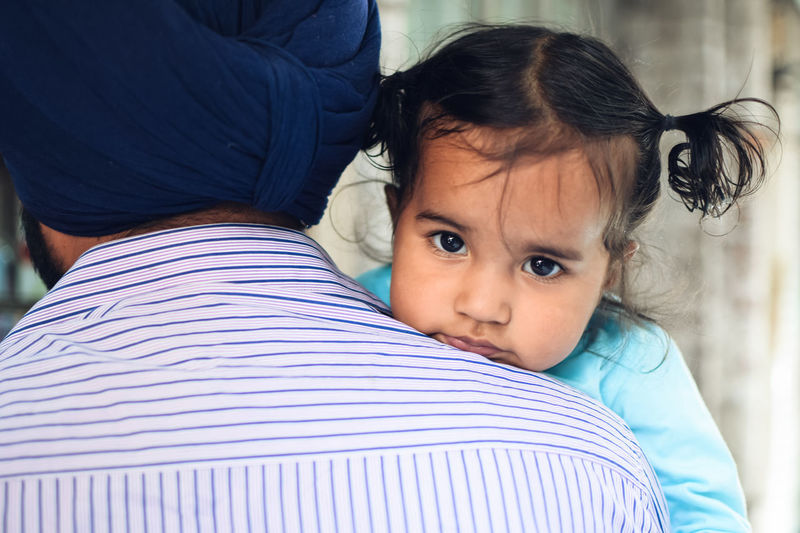 Rear view of father carrying cute daughter at home