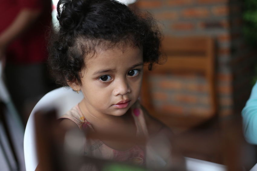 A little curly girl wondering while seated in high chair in the kitchen Child Childhood Cute Daughter Domestic Life Family Girl Girls Hanging Out Home Interior Horizon INDONESIA Indoors  Kitchen Lifestyles Mother Not Looking At The Camera One People People Photography Portrait Preschool Age Real People Women