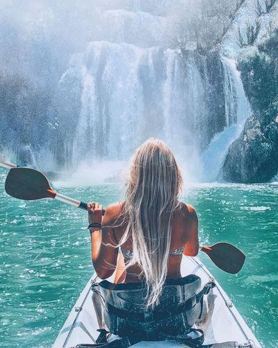 Rear view of woman splashing water