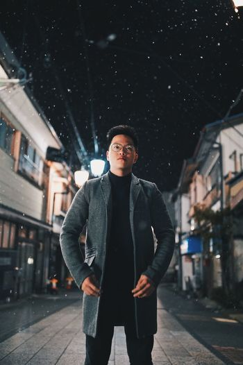 Portrait of young man standing in city at night
