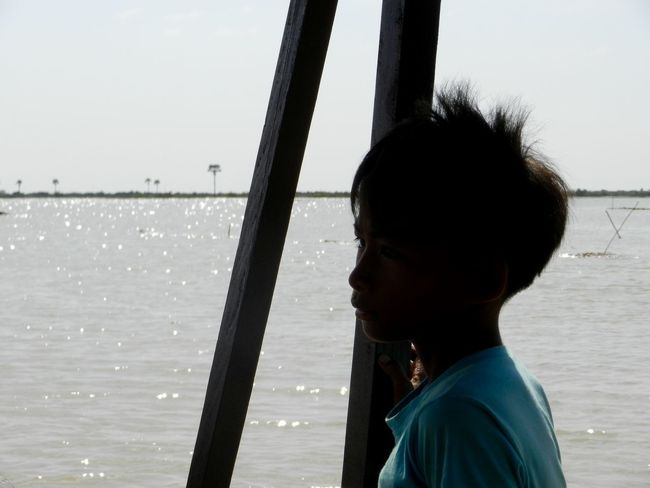 Boy on Boat Working Helping Thoughtful Reflections Water Child Boat Poverty Silhouette Tonlesap Cambodia