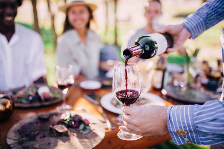 Alcohol Food And Drink Refreshment Drink Wineglass Wine Glass Men Holding Table Red Wine Leisure Activity Togetherness Lifestyles Group Of People Women Adult Celebration Food Human Hand Hand Drinking