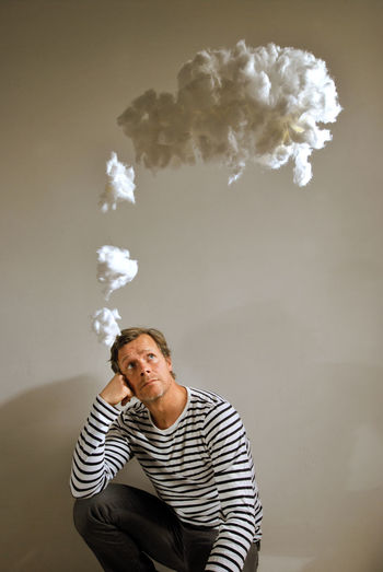 Thoughtful Man With Cotton In Mid-Air Against Gray Background