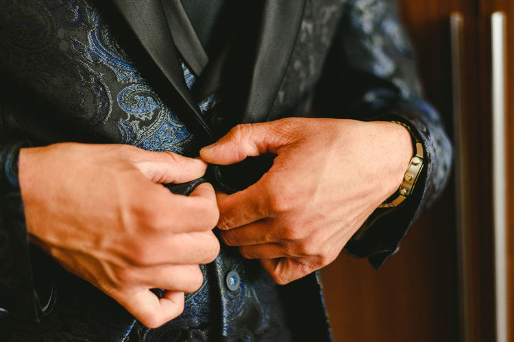 Midsection of man getting dressed