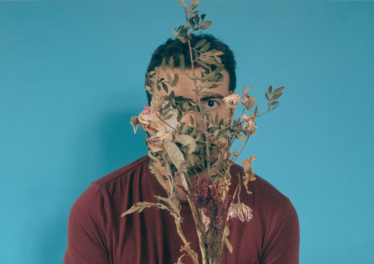 Close-Up Portrait Of Man With Dry Plants Against Blue Background