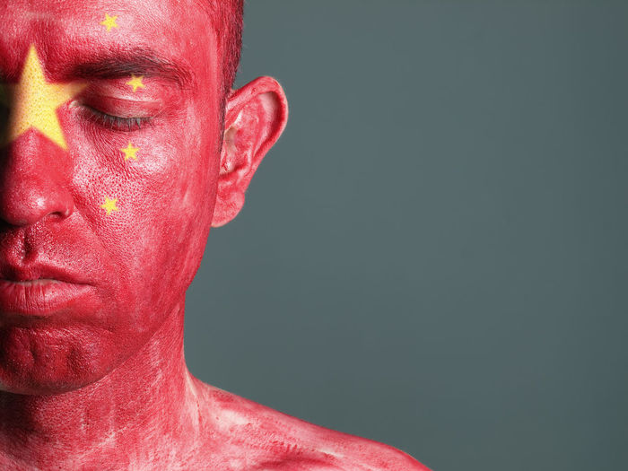 Close-up of man with chinese flag body paint against gray background