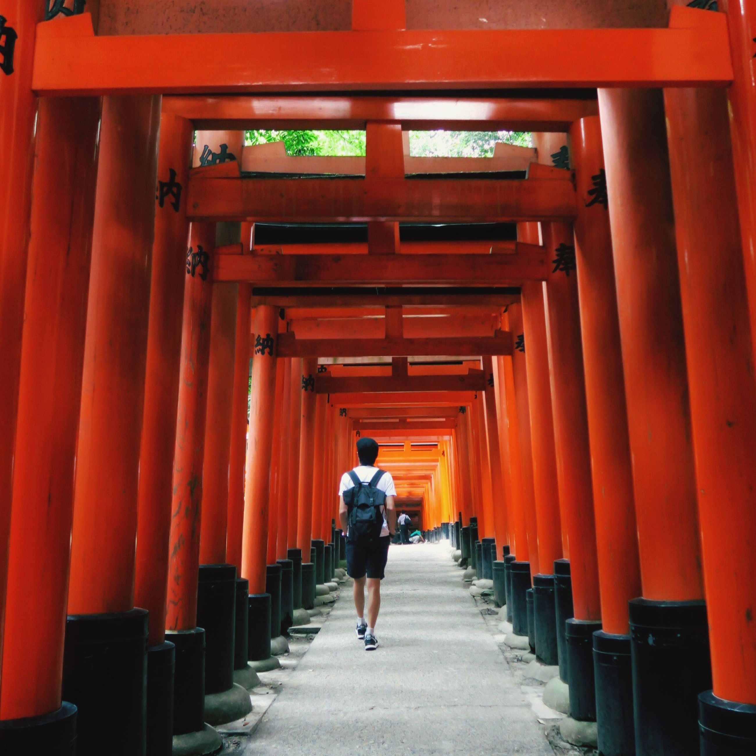 the way forward, built structure, architecture, in a row, men, rear view, walking, lifestyles, orange color, person, red, building exterior, full length, diminishing perspective, religion, temple - building, leisure activity, architectural column