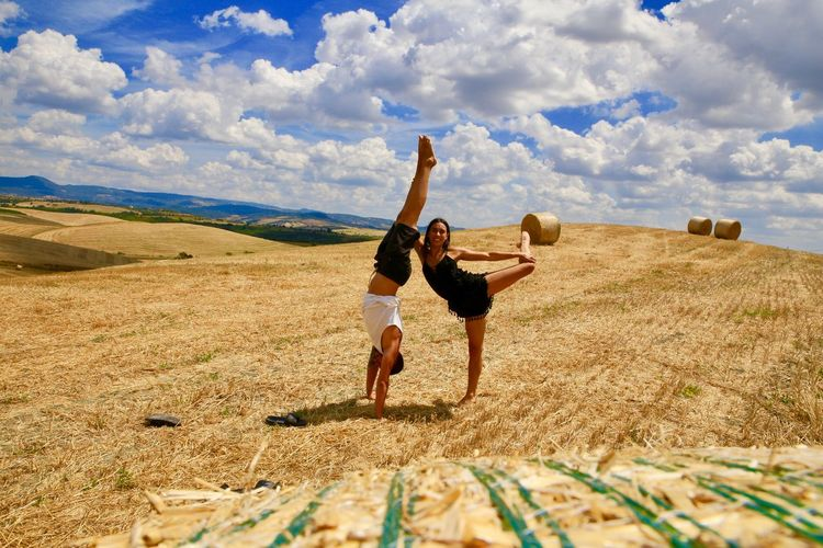 Full length of man doing handstand by young woman on agricultural field