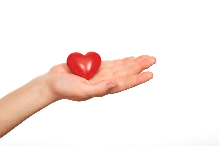 Close-up of hand holding heart shape against white background