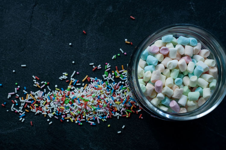 High angle view of multi colored candies and sprinkles on slate