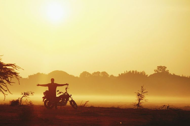 Man Standing By Motorcycle On Field Against Clear Sky