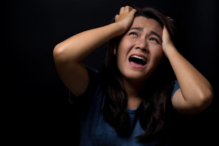 Scared Young Woman Screaming While Standing Against Black Background