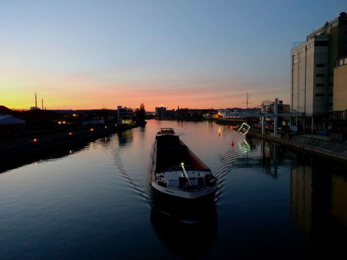 High angle view of barge sailing on river in city against sky during sunset