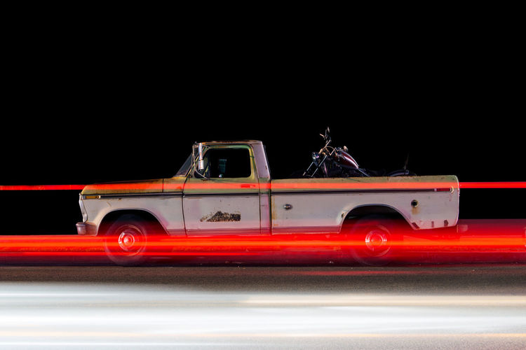 Side view of a vintage classic pick up truck car and light trails caused by traffic in Venice, California at night Blurred Motion Car City Copy Space Illuminated Land Vehicle Mode Of Transportation Motion Motor Vehicle Night No People Outdoors Red Road Speed Street Tail Light Transportation Truck