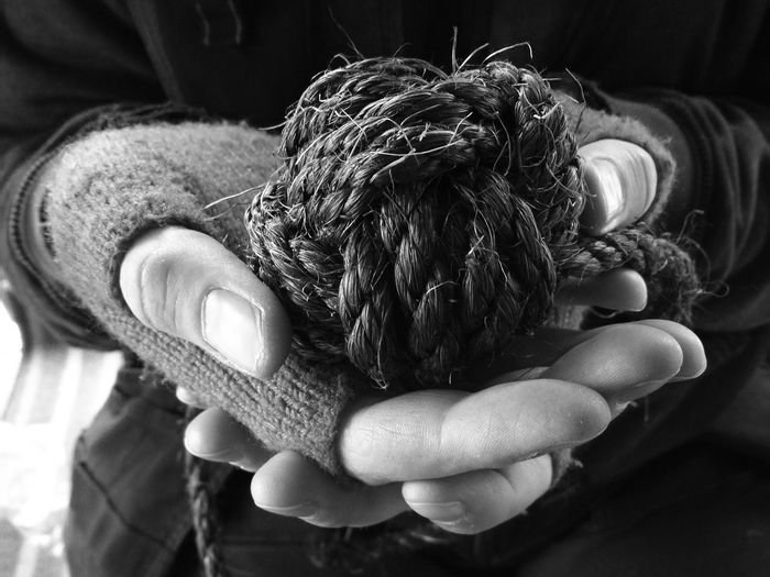 Midsection of person holding rope