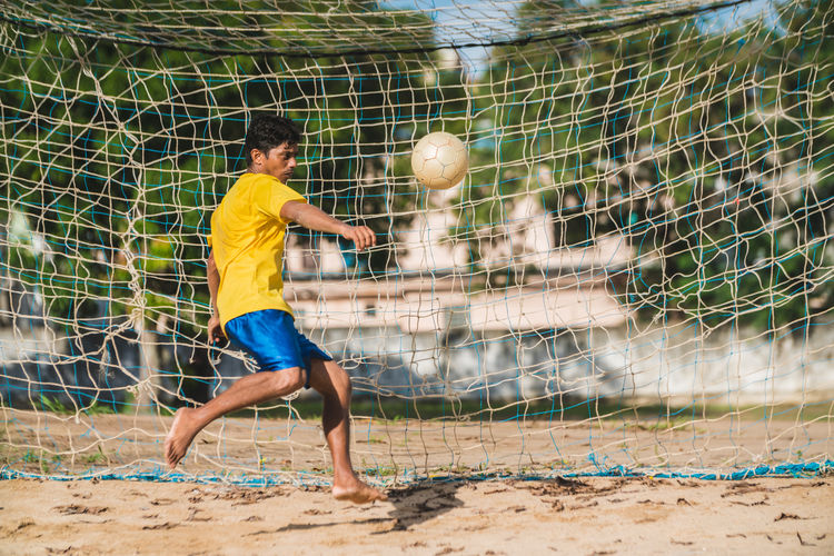 Soccer player showing his skill playing in the sand field in northeastern of Pernambuco, Brazil. 2018 Adult Brazil Field Goalie Pernambuco Skill  Ball Brazilian Cultures Goalkeeper Kicking Motion Northeast Playing Sand Soccer Soccer Ball Soccer Field Soccer Goal Soccer Life Soccer Player Soccer Uniform