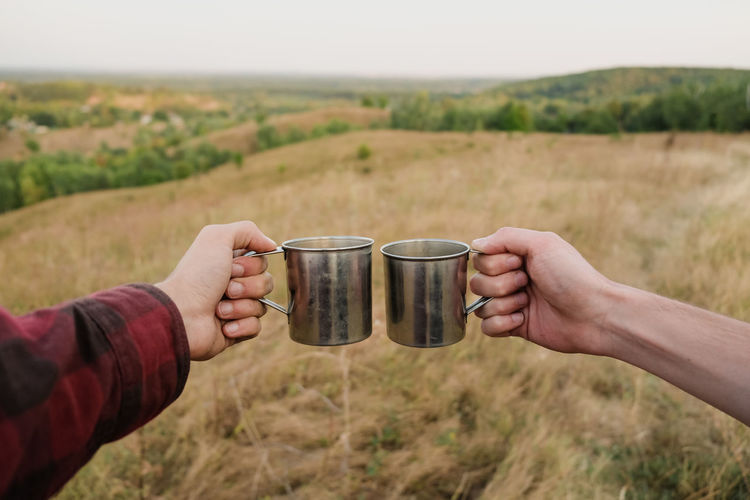 Cropped hands toasting cups over land against sky