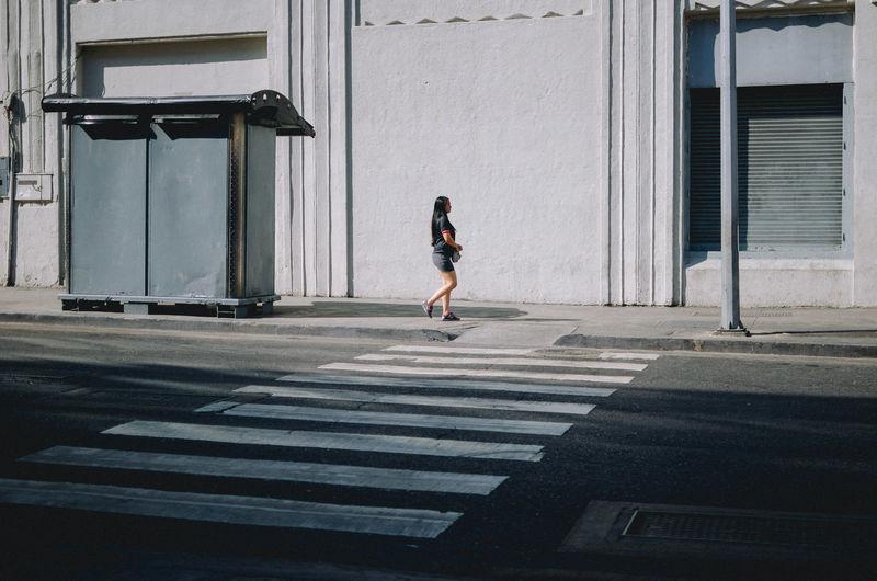 Full length of woman walking on street against building