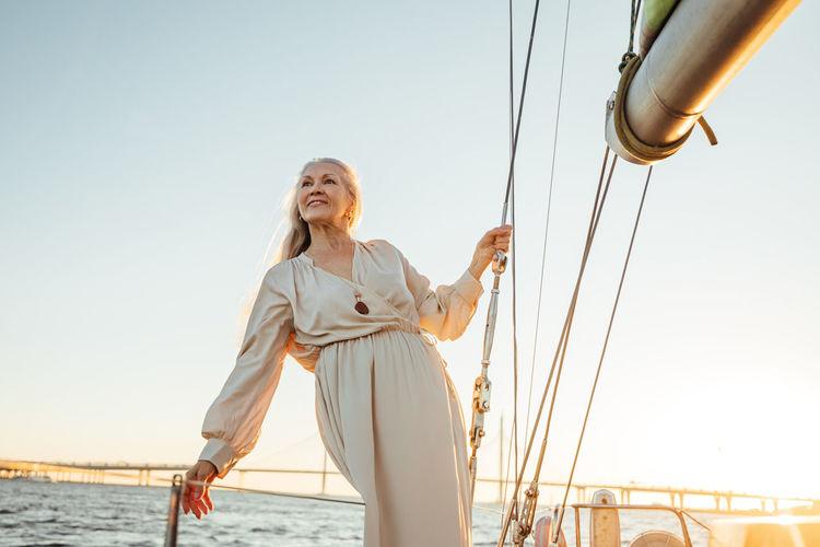 Senior woman standing at sailboat in sea