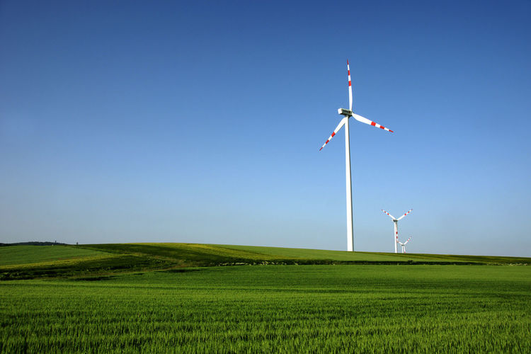Wind turbines on grassy field against clear sky