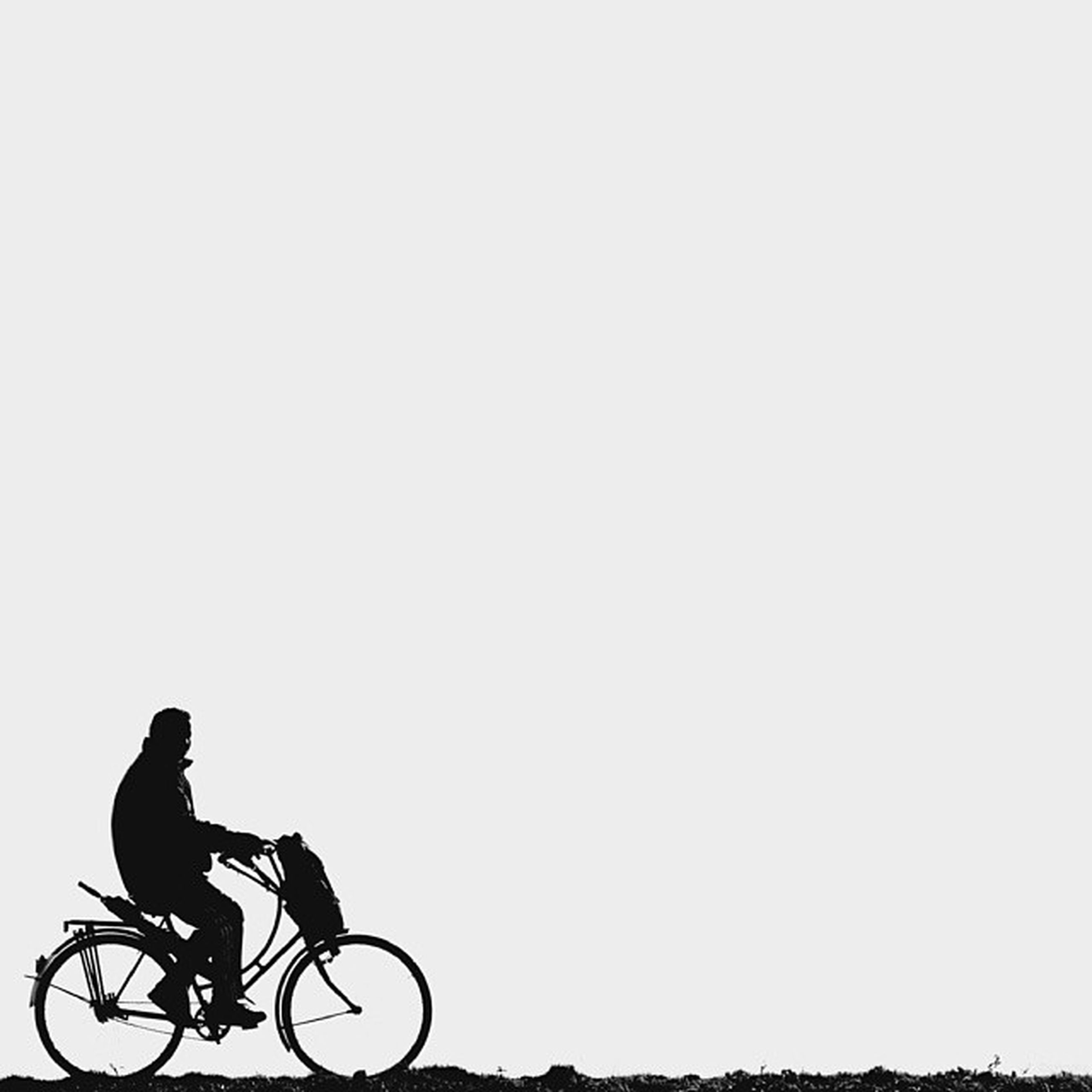 bicycle, land vehicle, transportation, mode of transport, copy space, clear sky, riding, stationary, parked, cycling, parking, side view, full length, silhouette, day, motorcycle, outdoors, road, travel, street