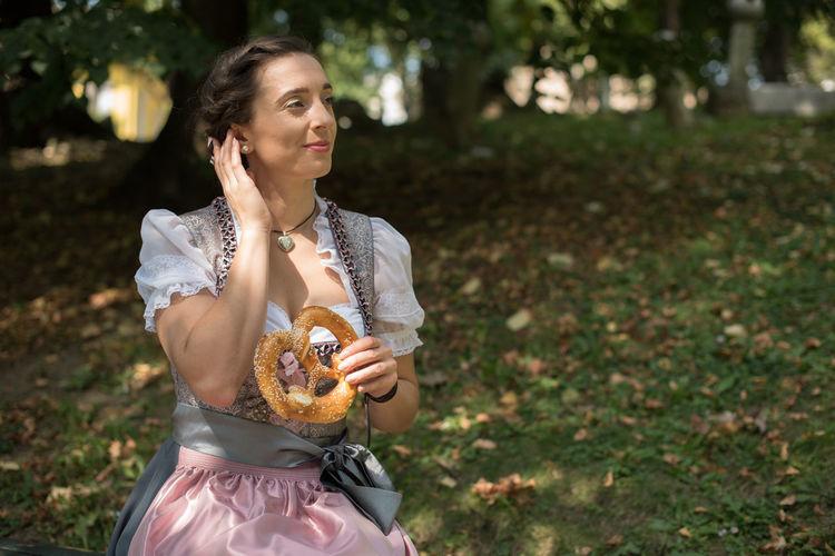Woman having pretzel while sitting on field