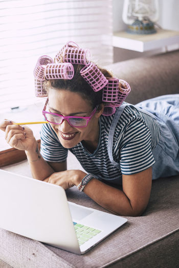 Woman with hair curlers using laptop at home