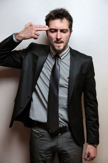 Young Businessman Gesturing Against Wall