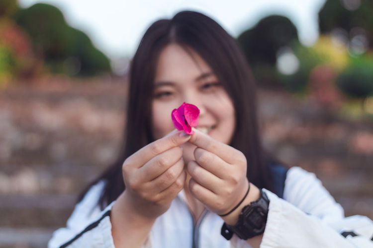 Portrait of woman holding pink while standing outdoors