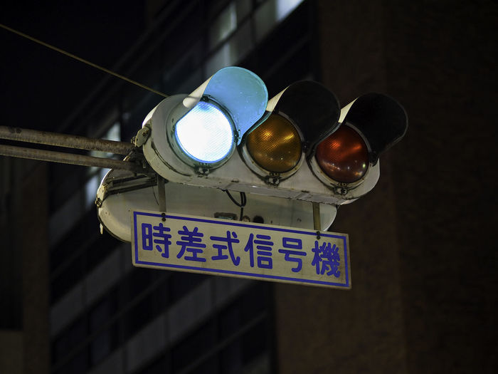 Low Angle View Of Road Signal Against Buildings