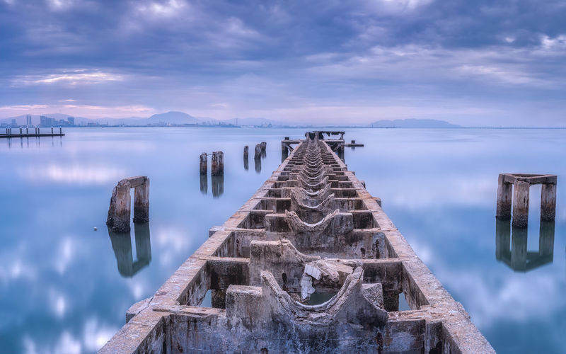 Panoramic view of wooden post in sea against cloudy sky