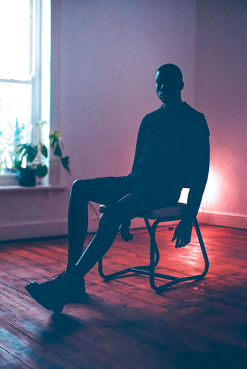 Silhouette man sitting on chair at home