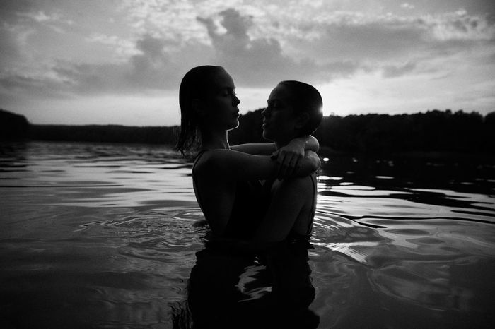 REAR VIEW OF MOTHER AND SON AT SWIMMING POOL AGAINST SKY