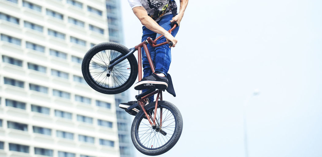 Low Section Of Man Practicing Stunt On Bicycle Against Clear Sky