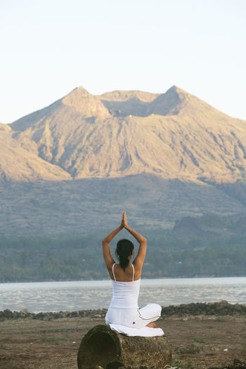 Woman practicing yoga on field against mountain