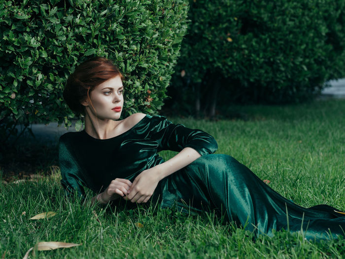 Young woman looking away while lying on grass