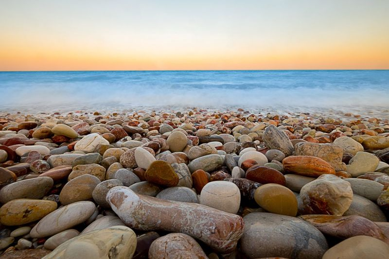 Rocks at beach against sky during sunset