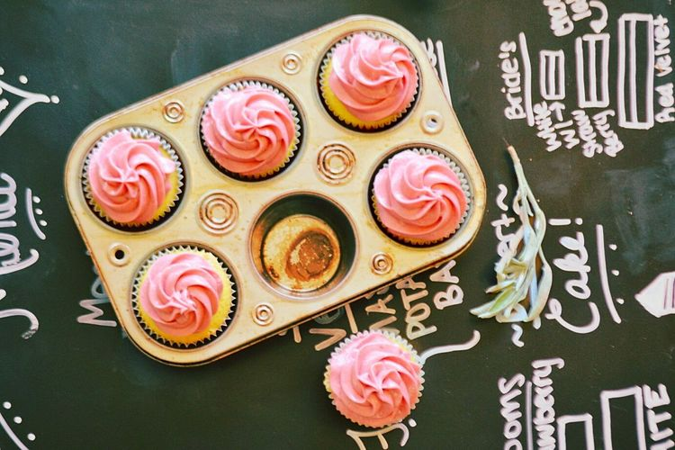 High Angle View Of Cupcakes In Baking Pan On Chalkboard